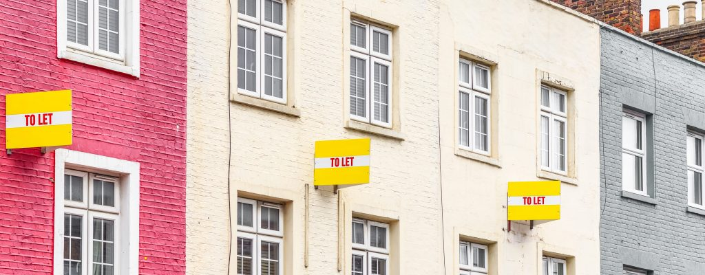 Three identical 'To Let' signs hang on terrace houses