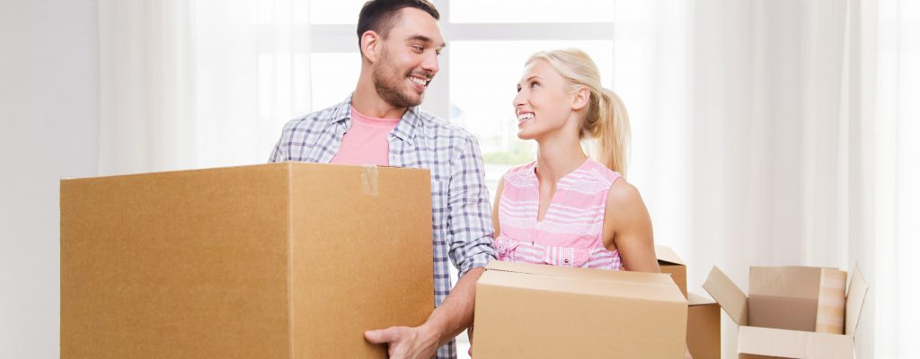 A young couple of first time buyers look at each other after purchasing their first home